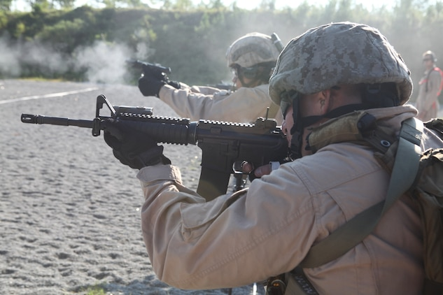 Marines fire their weapons during a timed drill as part of the Special Operations Training Group's Close Quarters Tactics course Aug. 31, on Stone Bay's Multi Purpose Range. The course is part of a pipeline of courses, conducted by SOTG, meant to prepare the Marines for the missions they may conduct while deployed with the 24th Marine Expeditionary Unit.