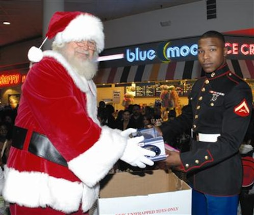 Santa Claus helps Lance Cpl. Marcus A. Andrews, Detachment 2, I-I, collect toys during a Toys for Tots toy drive at the Albany Mall, Nov. 18.