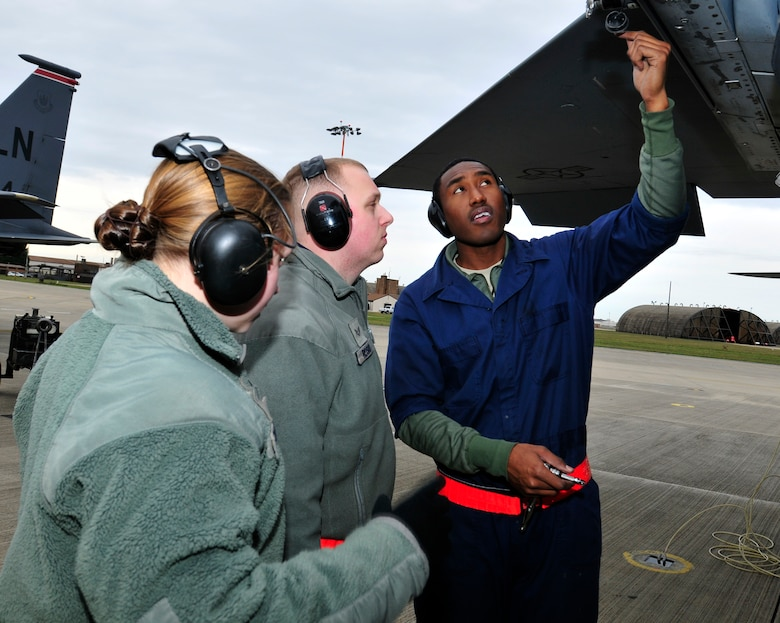 ROYAL AIR FORCE LAKENHEATH, England – (left to right) Airman 1st Class Ashton Colburn, 748th Aircraft Maintenance Squadron weapons team member, Senior Airman Timothy Rosio, 48th Aircraft Maintenance Squadron weapons team member and Staff Sgt. Arthur Belvin, 48th AMXS weapons load crew chief, perform an operations check on an F-15 Eagle on the flightline, Dec. 1, 2011. These Airmen contributed to the accomplishments which helped lead to Capt. William Bernecker, former 48th AMXS Officer in Charge, being awarded the Gen. Lew Allen Jr.Trophy. (U.S. Air Force photo by Senior Airman Tiffany M. Deuel)