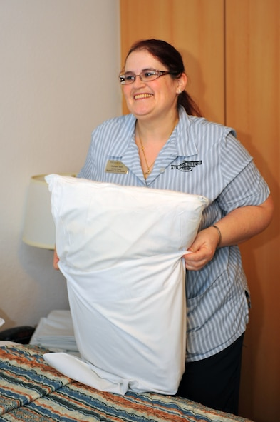 SPANGDAHLEM AIR BASE, Germany – Michaela Back, Eifel Arms Inn custodial worker, puts a clean pillow case on a pillow during a daily room cleaning in Bldg. 409 here Nov. 30. Eifel Arms Inn recently changed its policy to allow customers to make reservations more than 30 days in advance in an effort to improve their occupancy and quality of service. (U.S. Air Force photo/Airman 1st Class Dillon Davis)