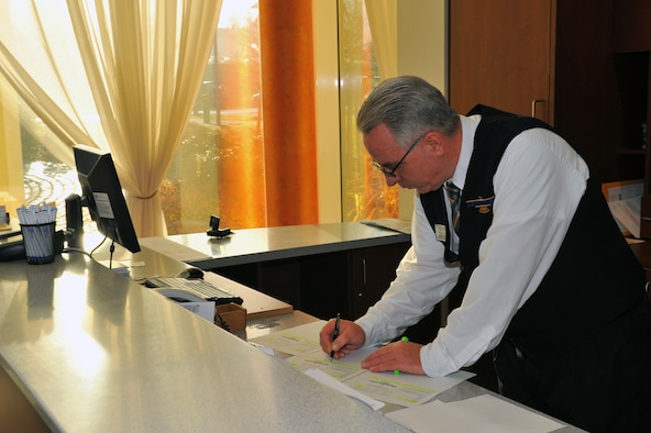 SPANGDAHLEM AIR BASE, Germany – Tracy Hatch, Eifel Arms Inn guest services representative, prepares reservation paperwork at the reception desk here Nov. 30 for a group of Soldiers laid-over from a deployment return. Eifel Arms Inn recently changed its policy to allow customers to make reservations more than 30 days in advance in an effort to improve their occupancy and quality of service. (U.S. Air Force photo/Airman 1st Class Dillon Davis)