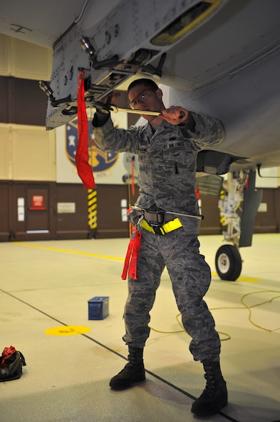 SPANGDAHLEM AIR BASE, Germany – Airman 1st Class Eric Williams, 52nd Aircraft Maintenance Squadron load crew member, prepares an A-10 Thunderbolt II's MAU-40 bomb rack during a monthly munitions loading evaluation here Nov. 29. The evaluation ensures load-crew members and team chiefs retain their qualification to load all munitions and are ready for mission taskings. Crew members complete an evaluation every month and are required to be evaluated annually while wearing chemical-warfare gear. (U.S. Air Force photo/Airman 1st Class Dillon Davis)