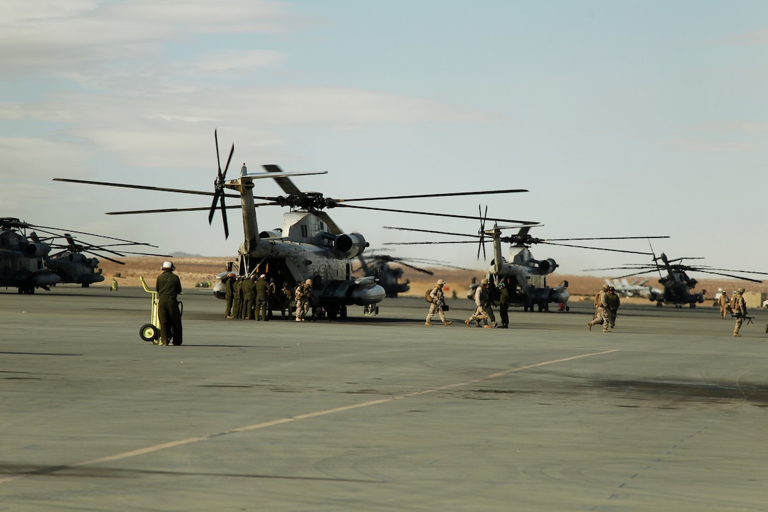 Marines hop off of a CH-53E Super Stallion  as aviation maintenance Marines prepare to do a daily turnaround inspection Dec. 2, 2011, at Camp Wilson. The inspection is conducted after every aircraft has landed.
