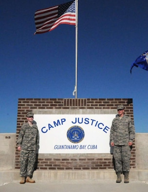 Sisters Army Staff Sgt. Rebecca Abbott and Air Force Master Sgt. Kelly Abbott pose in front of the sign at Camp Justice, Guantanamo Bay, Cuba. Rebecca flew down as a promise to her sister Kelly to help pin on her stripes during her promation to an E-7 during Kelly's deployment to GITMO.