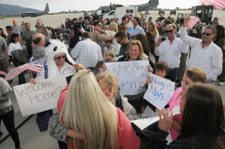 Family members of airmen returning from an overseas deployment hold up 'Welcome Home' signs and embrace their loved ones from the 146th Airlift Wing at Channel Islands Air National Guard Station on November 23, 2011. Members returned home from a 90 day AEF rotation in Afghanistan, just in time for Thanksgiving.