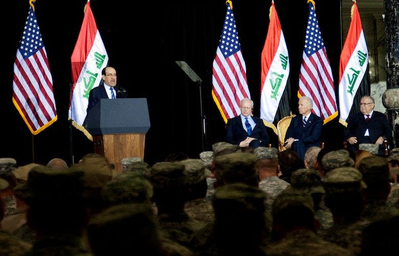 The Prime Minister of Iraq, Nouri Al-Maliki, gives a speech during the Commitment Day ceremony in the Al Faw Palace at Victory Base Complex, Iraq, on Dec. 1, 2011. The Government of Iraq hosted the ceremony to commemorate the sacrifices and accomplishments of U.S. and Iraqi service members. Ambassador to Iraq, James F. Jeffrey (left) and Vice President of the United States, Joe Biden (middle), and the President of Iraq, Jalal Talabani (right), were present on the stage during the ceremony. (U.S. Air Force photo/Master Sgt. Cecilio Ricardo)