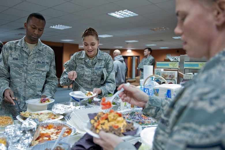 Senior Airman Thomas Jean, 39th Communications Squadron postal clerk, left, and Senior Airman Brianna Bergstrand, center, 39th Air Base Wing knowledge operator, get food from Master Sgt. Jamie Eichhorn, 39th Security Forces Squadron logistics superintendent, during a free Airman's dinner at The Connection Dec. 1, 2011, at Incirlik Air Base, Turkey.  The Connection, a building and program run by the 39th Air Base Wing Chapel, provides unaccompanied Airmen sanctuary from the hectic bustle outside the building's walls. (U.S. Air Force photo by Senior Airman Anthony Sanchelli/Released)