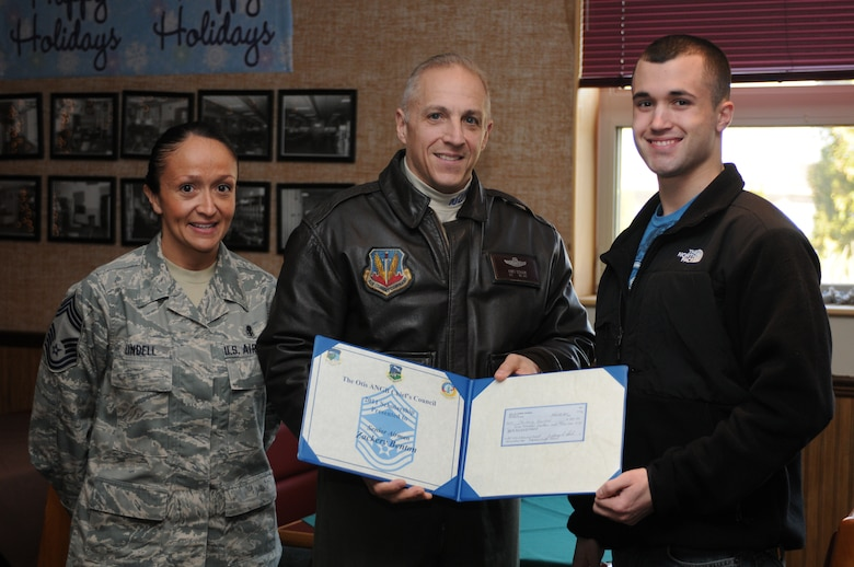 On December 3, 2011, Senior Airman Zackery Benton receives a 500 dollar scholarship from the Chief's Council during a ceremony at Arnold Hall. The scholarship is awarded annually to deserving airmen and families of 102nd Intelligence Wing.  (National Guard photo by Senior Airman Jeremy Bowcock/Released)