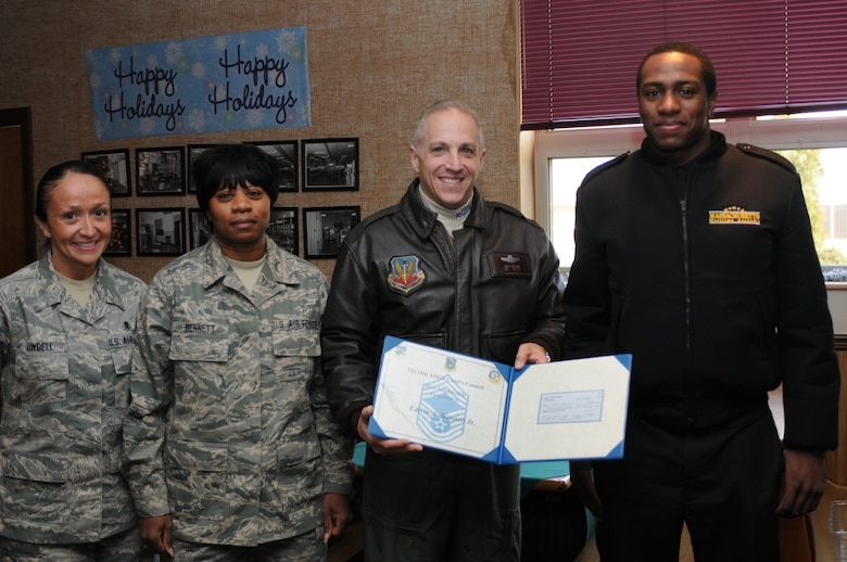 On December 3, 2011, Edwin Bennett Jr. receives a 500 dollar scholarship from the Chief's Council during a ceremony at Arnold Hall. The scholarship is awarded annually to deserving airmen and families of 102nd Intelligence Wing.  (National Guard photo by Senior Airman Jeremy Bowcock/Released)