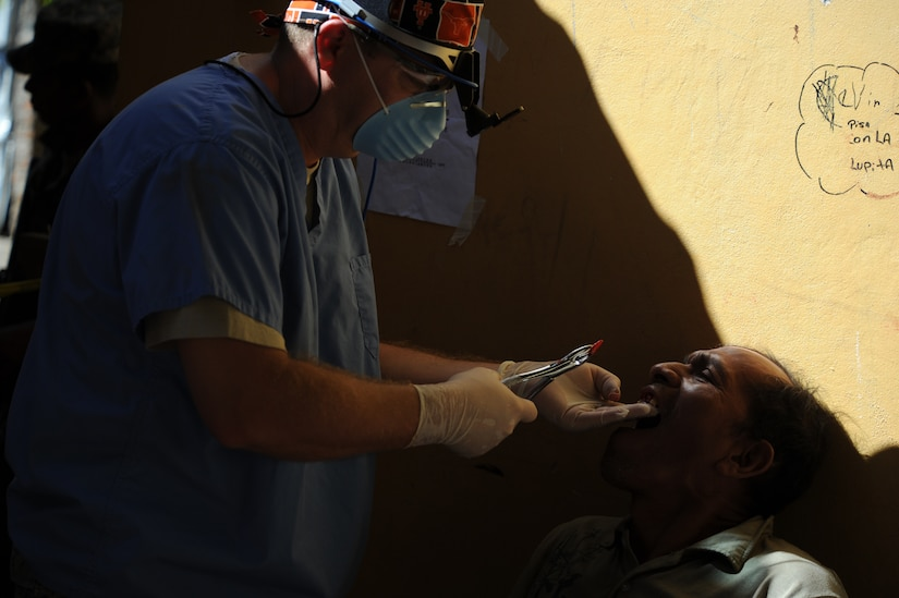 Maj. David Dennison, a Joint Task Force-Bravo Medical Element general dentist, pulls a tooth of a Honduran man during a Medical Readiness Training Exercise Nov. 29, 2011, at a school in Choluteca, Honduras.  By the end of the two-day mission, the U.S. and Honduran medical staff combined achievements included the assistance of nearly 150 dental patients, the filling of more than 2000 pharmacy prescriptions, and the education of over 1,100 people in preventative medicine. (U.S. Air Force photo/Tech. Sgt. Matthew McGovern)