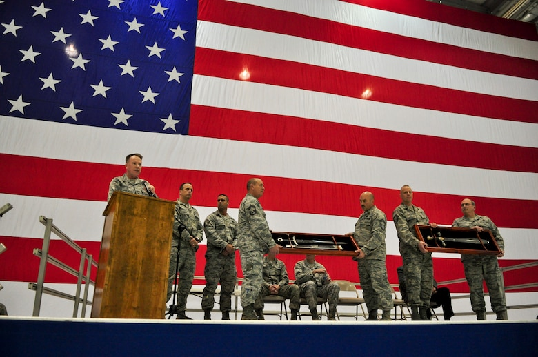 From the podium, Col. Ted Metzgar, commander of the 128th Air Refueling Wing, presents two etched swords to Command Chief Master Sgt. Joe Parlato, command chief of the 128th Air Refueling Wing, and Master Sgt. Mike Schmaling, 1st Sgt. of the 128th Mission Support Group, during a Hometown Heroes Salute Campaign award ceremony at the 128th Air Refueling Wing, Milwaukee, on Sunday, December 4, 2011.  The swords were purchased in Spain, and they were presented to the recipients on behalf of the 128th Air Refueling Wing and 313th Air Expeditionary Wing.  The Hometown Heroes Salute Campaign is an Air National Guard event that recognizes Airmen who have deployed overseas for more than 30 days.  Air National Guard photo by Tech. Sgt. Tom Sobczyk.