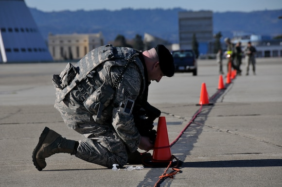 California Air National Guard Senior Airman Clinton Bailey, 129th Rescue Security Forces Squadron, marks off a restricted area around aircraft at Moffett Federal Airfield, Calif., Dec. 4, 2011. Senior Airman Bailey is taking part in the 129th Rescue Wing's Operational Readiness Inspection, which tests the unit's wartime capabilities and readiness to deploy. (Air National Guard photo by Staff Sgt. Kim E. Ramirez)
