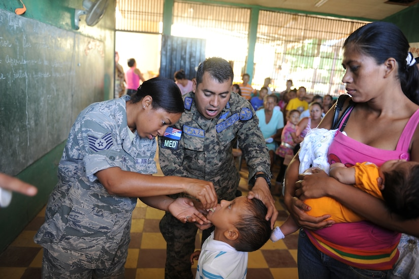Tech. Sgt. Michelle James, from Joint Task Force-Bravo Medical Element and Honduran Army Sgt. Maj. Ovidio Paz-lagos, a nurse from the Honduran Surgeon Generals Office, give anti-parasitic medication to a Honduran boy during a Medical Readiness Training Exercise Nov. 30, 2011, in the department of Choluteca, Honduras.  (U.S. Air Force photo/Tech. Sgt. Matthew McGovern)