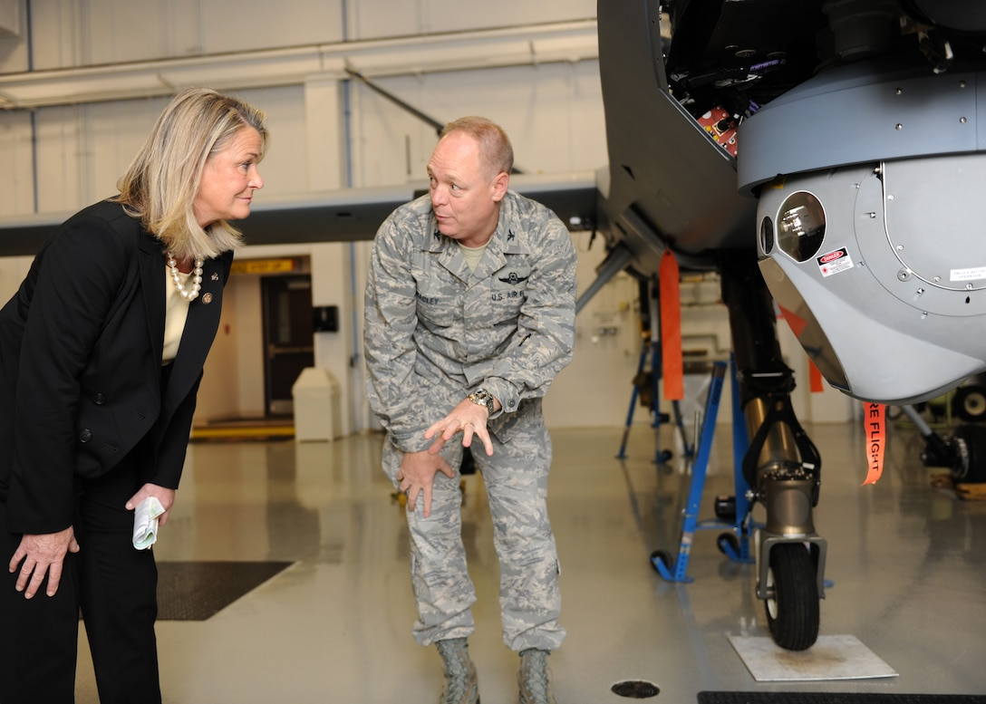 U.S. Rep. Ann Marie Buerkle, 25th District New York, receives a briefing about the capabilities of the MQ-9 Reaper remotely piloted aircraft from 174th Fighter Wing Commander, Col Kevin W. Bradley, during a visit to Hancock Field Air National Guard Base on 4 Dec 2011. (Photo by New York Air National Guard Tech. Sgt. Ricky Best/Released)