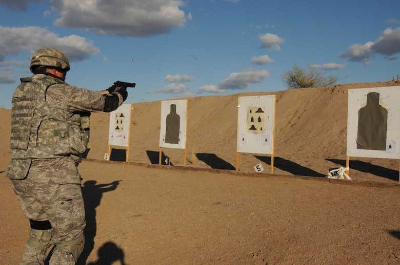 Capt. David Foulke, 161st Security Forces Squadron commander, practices transitioning to the handgun during weapons qualification Dec. 5, 2011, at the National Guard training range in Florence, Ariz. Beginning Dec. 1, 2011, all Airmen are required to perform in the modernized rifle qualification course which comprises movement while engaging targets to better train and equip Airmen. (U.S. Air Force photo/Tech. Sgt. Susan Gladstein)