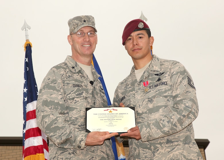 Brig. Gen. Timothy Zadalis, Air Education and Training Command Intelligence, Operations and Nuclear Integration director from Randolph AFB awards Tech. Sgt. Luis Garcia, 342nd Training Squadron pararescueman, with a Bronze Star Medal with Valor during an award ceremony at Lackland Air Force Base, Texas, Dec. 2. Only 414 Bronze Star Medals with Valor have been awarded to Air Force service members since Sept. 11, 2001. (U.S. Air Force photo/Robbin Cresswell)