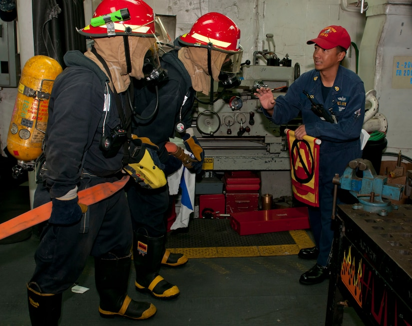 Chief Petty Officer Eugene Ruelos instructs Sailors on the proper procedure for entering a space that had reports of fire during a ship-wide survivability training aboard the Arleigh Burke-class guided-missile destroyer USS Stethem (DDG 63). Stethem is operating in the western Pacific region. (U.S. Navy photo/Petty Officer 3rd Class Matthew Cole)