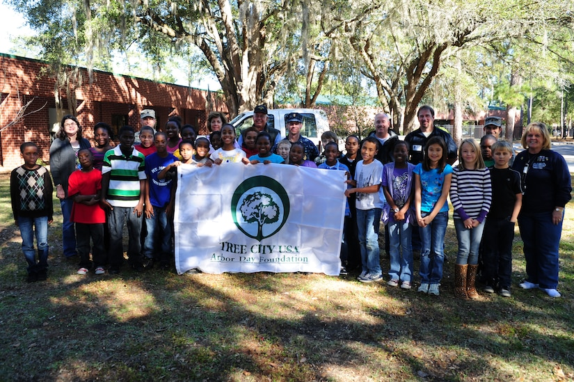 Lieutenant Col. Randall Bishop (sixth from left) and  Master Chief Petty Officer Billy Cady and other members of the 628th Civil Engineer Squadron, stand with members of the South Carolina Forestry Commission and students and faculty members during an Arbor Day ceremony at Hunley Park Elementary School Dec. 2. This is the 16th year JB Charleston has been a member of the Tree City USA foundation. To become a Tree City USA member, a community most meet four annual standards:  a tree protection board or manager, a tree care ordinance, a comprehensive community forestry program, and an Arbor Day observance.  Bishop is the 628 CES commander and Cady is the JB Charleston - Weapons Station command master chief.  (U.S. Air Force photo/ Staff Sgt. Nicole Mickle)
