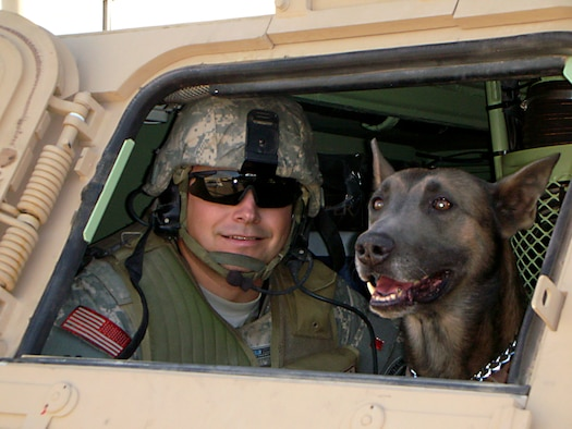 Master Sgt. Craig Young, former 95th Security Forces Squadron, and his then military working dog, Telin, take a break from a patrol while on deployment to Iraq in 2007 and 2008. Telin, a Belgian Malinois and former military working dog at Edwards, deployed three times during his military career. (Courtesy photo)