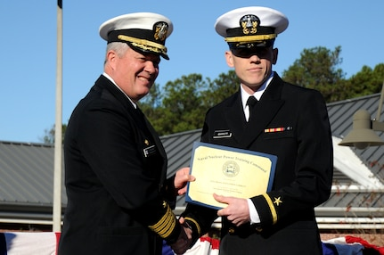 Ensign Miles Garrett receives the Vice Adm. Behrens award from Capt. Thomas Bailey during the Naval Nuclear Power Training Command graduation ceremony for class 1105 at Joint Base Charleston - Weapons Station Dec. 2. The Behrens award recognizes the graduating officer with the highest grade-point average. Garrett earned an overall GPA of 3.76. Bailey is the NNPTC commanding officer. (U.S. Navy photo/Petty Officer 2nd Class Brannon Deugan)