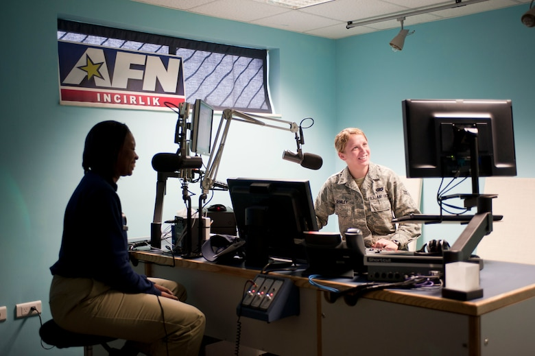 Airman 1st Class Laura Beckley, American Forces Network Incirlik, jokes with radio show guest Master Sgt. Tapika Bryant, 39th Force Support Squadron, before going on air Nov. 30, 2011, at Incirlik Air Base, Turkey. Bryant was on the show to give information about the fitness assessment cell and exercising in cold weather. (U.S. Air Force photo by Senior Airman Clayton Lenhardt/Released)