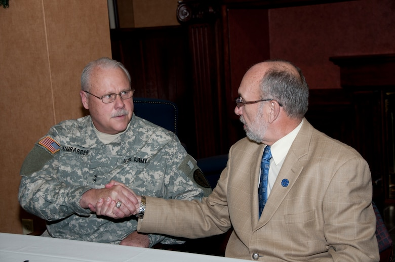 Terre Haute, Ind. – Maj. Gen. R. Martin Umbarger, The Adjutant General of Indiana, and Dr. Daniel J. Bradley, President, Indiana State University, shake hands after signing a memorandum of understanding at Indiana State University on December 5, 2011. The agreement allows ISU to use restricted air space, runways and other resources at Camp Atterbury-Muscatatuck Center for Complex Operation, in southeastern Indiana. Photo by Senior Master Sergeant John S. Chapman