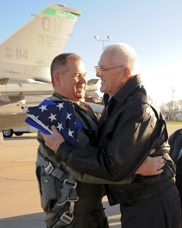 Lt. Col. Tim Moses, 180th FW Operations Support Squadron Commander, receives a hug from Walter Young after Moses presented Mr. Young with an Air Force flag in honor of Young's son, Lt. Mike Young. Moses carried with him an American flag and a United States Air Force flag and flew up the coast of Lake Huron and over the crash site, where a memorial in Lt. Young's name now stands. 180th Fighter Wing members, along with family and friends of pilot, Lt. Mike Young gathered for a small memorial honoring the pilot, 20 years after Young died when his A-7 Corsair crashed during a routine training mission. The group gathered at the 180th Fighter Wing, Ohio Air National Guard Base, Swanton, OH, Nov. 30.
