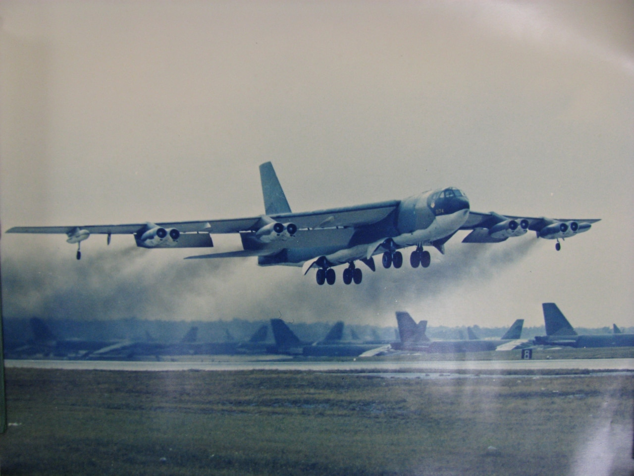 A B-52 Stratofortress bomber takes off from a runway.