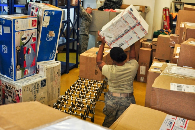 Senior Airman Meygan Freeney and Staff Sgt. Douglas Reedy, both postal clerks with the 51st Communications Squadron, work together to process and sort some packages here Dec. 6, 2011. The Military Postal Service Agency here processes about 3,000 pieces of mail a day during the holiday season. (U.S. Air Force photo/Tech. Sgt. Chad Thompson)