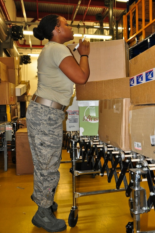 Senior Airman Meygan Freeney, a postal clerk with the 51st Communications Squadron, processes some packages at the post office here Dec. 6, 2011. The Military Postal Service Agency here processes about 3,000 pieces of mail a day during the holiday season. (U.S. Air Force photo/Tech. Sgt. Chad Thompson)