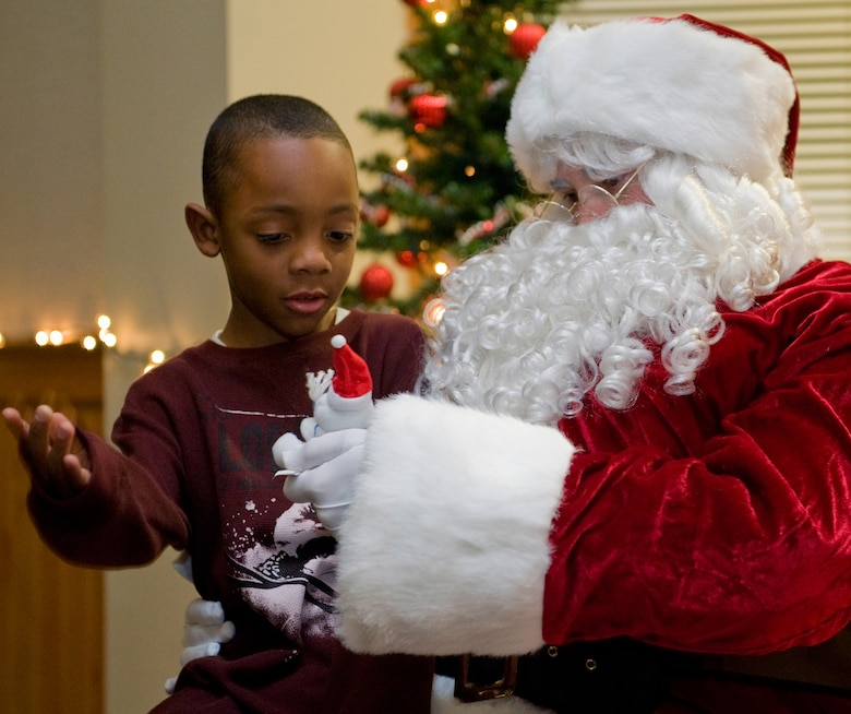 Santa hands Trabeon Wilcher, 7, a toy after hearing what Wilcher wanted for Christmas. Children of all ages were able to sit on Santa's lap during Malmstrom holiday festivities. (U.S. Air Force photo/Beau Wade)