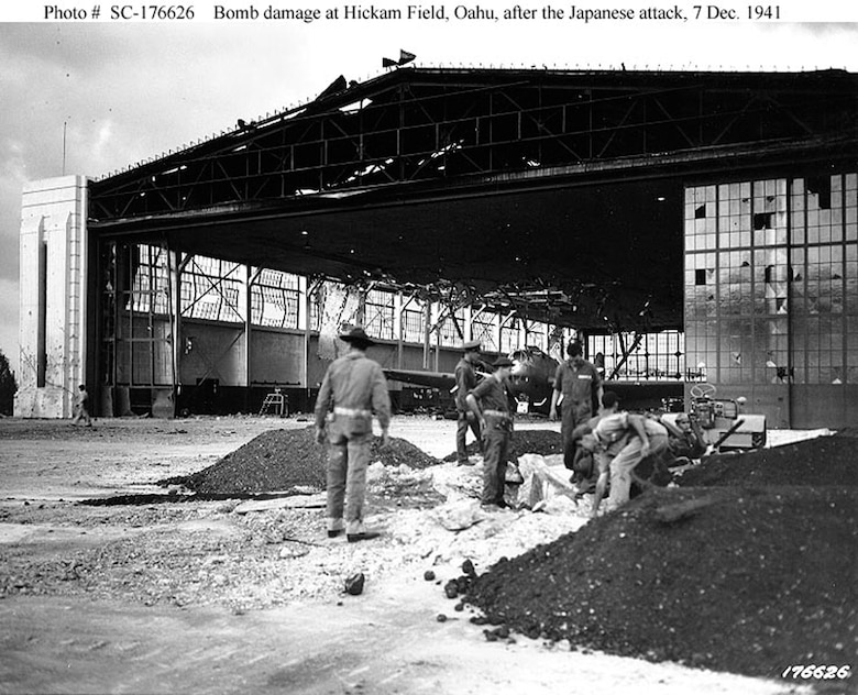 Bomb damage to Hangars 15-17 and 11-13 at Hickam Field, Oahu, at 5PM on Dec. 7, 1941. In the right foreground is a machine gun emplacement in a bomb crater.  A Douglas B-18 bomber is visible inside the badly damaged hangar. (Courtesy Photo/Air Force Historical Research Agency)