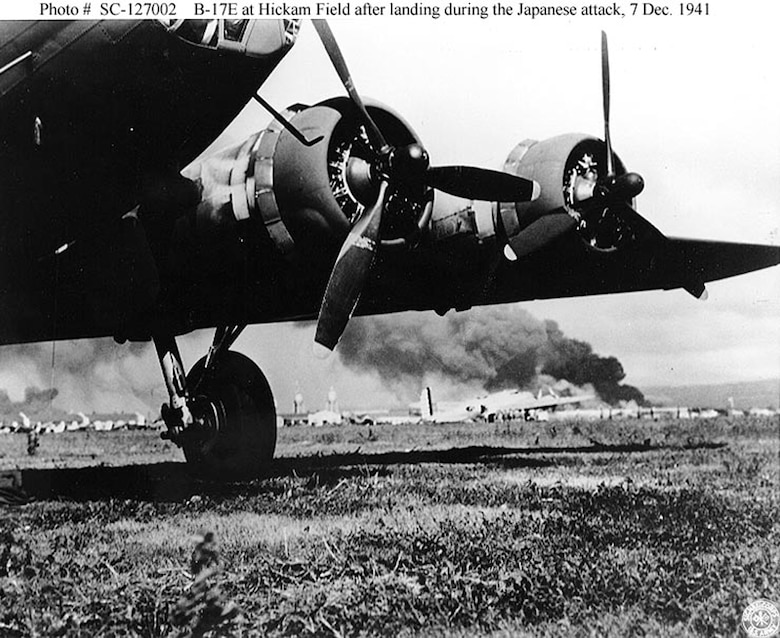A U.S. Army B-17E at Hickam Air Field, after landing safely during the Japanese air raid. In the background is a B-17C (or B-17D). Smoke from burning ships at Pearl Harbor is visible in the distance. (Courtesy Photo/Air Force Accessions)