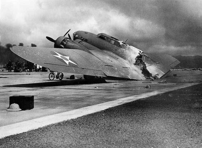 A burned U.S. Army Air Corps Boeing B-17C Flying Fortress (s/n 40-2074) rests near Hangar 5, Hickam Field, Hawaii, on 7 December 1941. It was one of 12 flown to Hickam from Hamilton Field, Calif., and arrived during the attack. On its final approach, the aircraft's magnesium flare box was hit by Japanese strafing and ignited. The burning plane separated upon landing. The crew survived the crash, but a flight surgeon was killed by strafing as he ran from the burning wreck. (Courtesy Photo/National Archives and Records Administration)