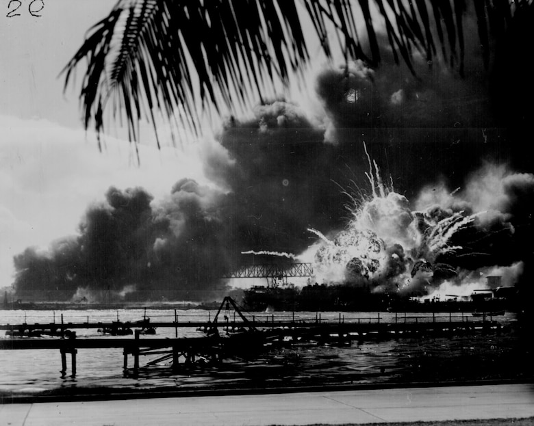 The forward magazine of USS Shaw (DD-373) explodes during the second Japanese attack wave. To the left of the explosion, Shaw's stern is visible, at the end of floating drydock YFD-2.  At right is the bow of USS Nevada (BB-36), with a tug alongside fighting fires. (Courtesy Photo/Naval History and Heritage Command)
