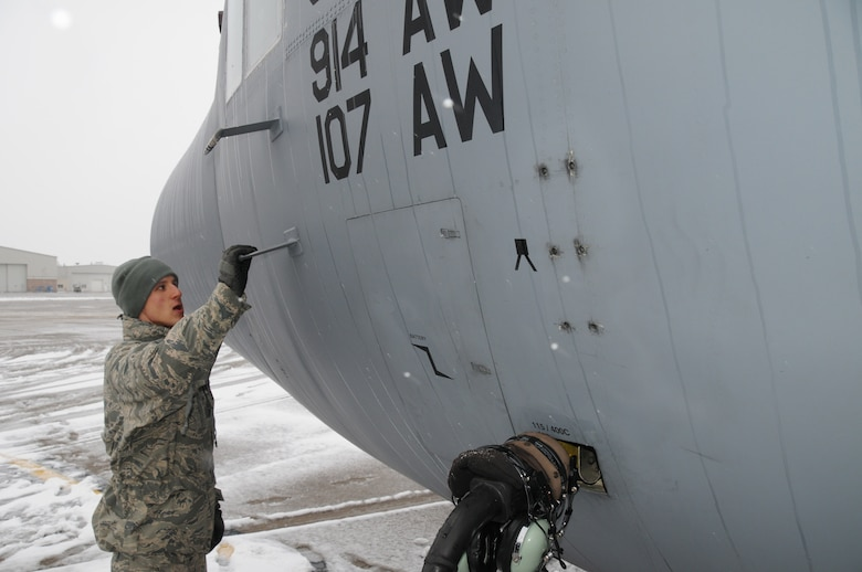 107th Crew Chief Airman 1st Class Nicholas Ruhland performs his aircraft precheck on the C-130 at the Niagara Falls Reserve Station while the lake effect storms hits the area on December 9, 2011. (Air Force Photo/SMSgt Ray Lloyd)