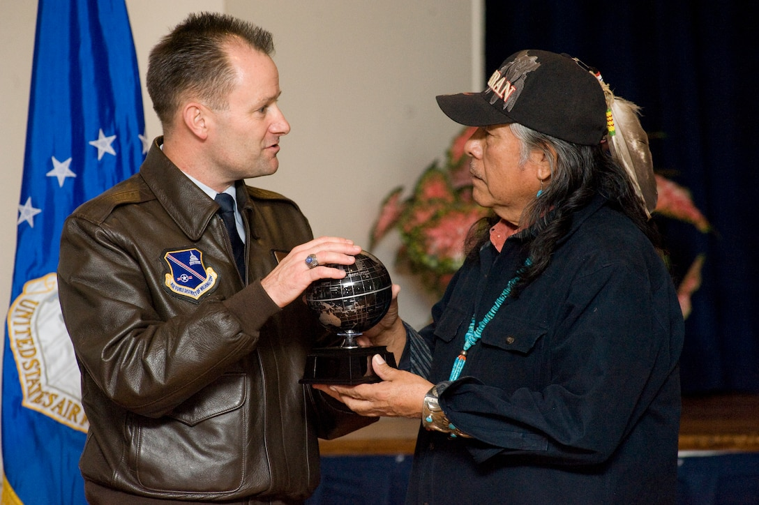 JOINT BASE ANDREWS, Md. -- Col. Ken Rizer, 11th Wing/Joint Base Andrews commander, presents Chuck Tsinnie, 11th Force Support Squadron marketing illustrator, with a parting gift for sharing his life story during an American Indian Heritage Month event at the Community Activity Center on Nov 30. (Photo/Bobby Jones)