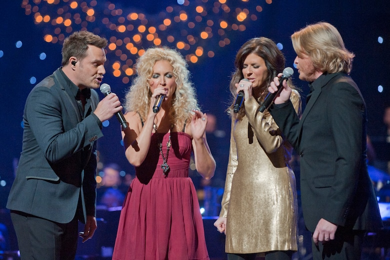 "Little Big Town members Jim Westbrook, Kimberly Schlapma, Karen Fairchild and Philip Sweet sing a holiday favorite during the taping of ""Holiday Notes from Home"" at the Grand Ole Opry House, Nashville, Tenn. The group joined Lee Ann Womack, the Band of the U.S. Air Force Reserve and the Air Force Strings to record the hour-long special that will air on the American Forces Network and the Great American Country Network this holiday season. (U.S. Air Force photo/Ken Hackman)"