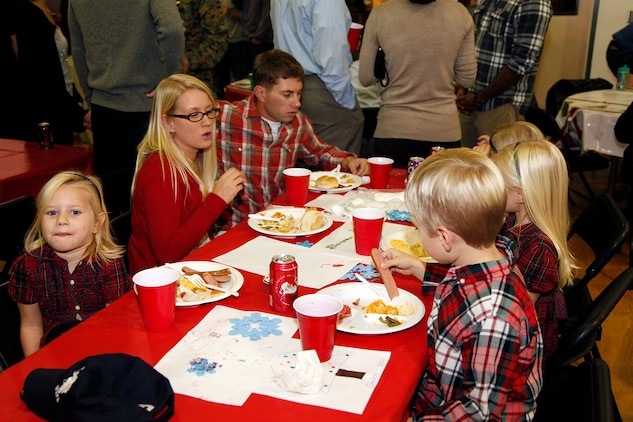 Staff Sgt. Robert L. Lower, fires chief, operations section, 15th Marine Expeditionary Unit, eats dinner with his family at the holiday party hosted at the Abby Reinke Community Center on base, Dec. 9. The event also gave the unit's leadership the opportunity to welcome the unit's new Family Readiness Officer, Rebecca Roman and bid farewell to Audrey Hooper, who served as the unit's FRO on the last deployment. During the holiday party the families enjoyed good food and company while Santa Claus passed out gifts and took photos with kids. (U.S. Marine Corps photo by Cpl. John Robbart III)