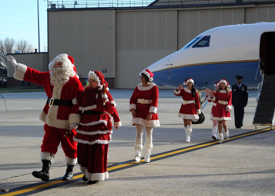 Mr. and Mrs. Santa Clause arrive in style to the Parents and Children Fighting Cancer holiday event in a C-37A aircraft. The Claus' were a special guest at the holiday event Dec. 3 where they distributed gifts to families. (U.S. Air Force photo/Senior Airman Bahja J. Jones)