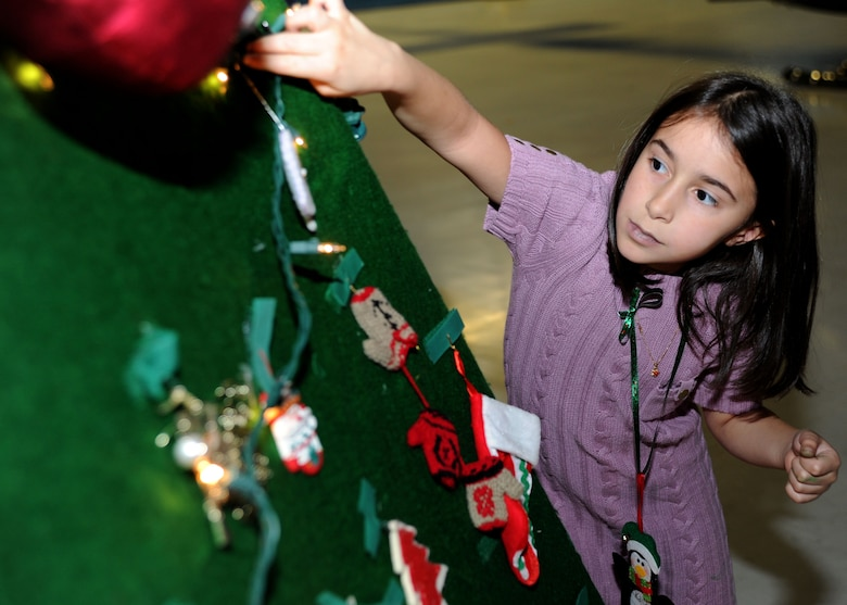 Kialani, 8, daughter of Karl Briales from Lorton, Va., places an ornament on a Christmas tree during the Parents and Children Fighting Cancer holiday event in Hangar 3 on Dec. 3. This is the third year the family has attended the holiday event. (U.S. Air Force photo/Senior Airman Bahja J. Jones)