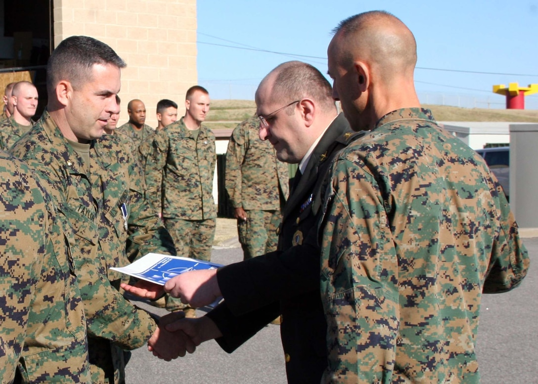 """Maj. Stephen J. Taylor, commanding officer of Headquarters Battalion, 2nd Marine Division, Camp Lejeune, N.C., receives the Republic of Georgia Ministry of Defense Award from Georgian Lt. Col. Lasha Beridze, deputy chief of defense, Republic of Georgia Ministry of Defense, during a ceremony at Marine Corps Security Cooperation Group, Virginia Beach, Va., on Dec. 13, 2011. Taylor received the award """"for outstanding support and dedication which contributed greatly to the overall success of the 3rd Georgian Brigade's mission in Afghanistan"""" from February to August 2011 while deployed to Afghanistan with Regimental Combat Team 2."""
