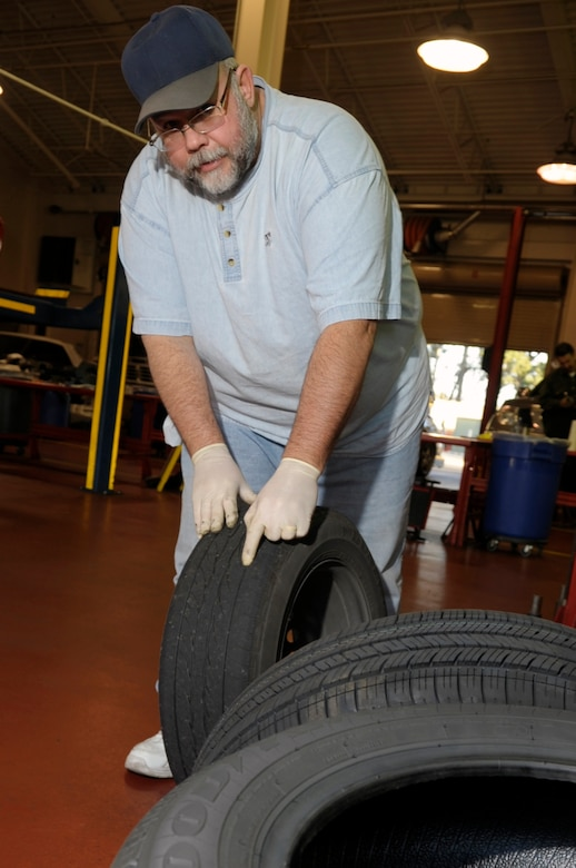 VANDENBERG AIR FORCE BASE, Calif. -- Eric Whittaker, a United Paradine contractor, shows us bad tread wear while changing tires at the auto hobby shop here Friday, Dec. 9, 2011. The auto hobby shop is open to customers with base access offering a variety of services and a knowledgeable staff to help with automotive projects. (U.S. Air Force photo/Jerry E. Clemens Jr.)