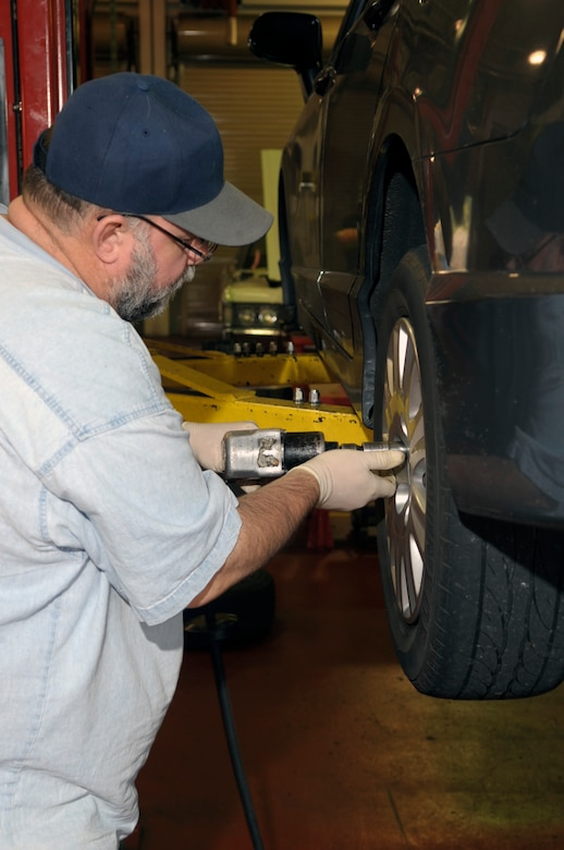VANDENBERG AIR FORCE BASE, Calif. -- Eric Whittaker, a United Paradine contractor, uses an air tool to change a tire at the auto hobby shop here Friday, Dec. 9, 2011. The auto hobby shop is open to customers with base access offering a variety of services and a knowledgeable staff to help with automotive projects. (U.S. Air Force photo/Jerry E. Clemens Jr.)