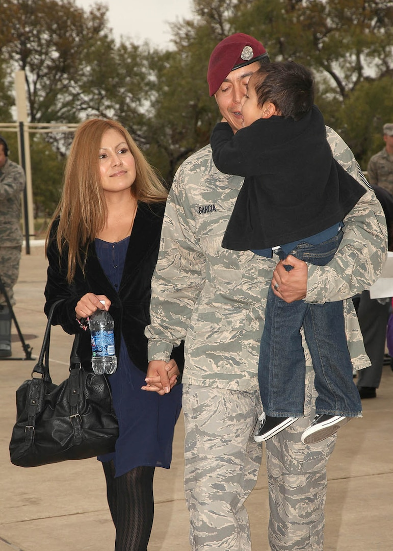 Tech. Sgt. Luis Garcia, with his wife, Brenda, son Mayan and daughter Zinnia (not pictured) arrive for the Bronze Star Medal with Valor presentation Dec. 2. (U.S. Air Force photo/Robbin Cresswell)