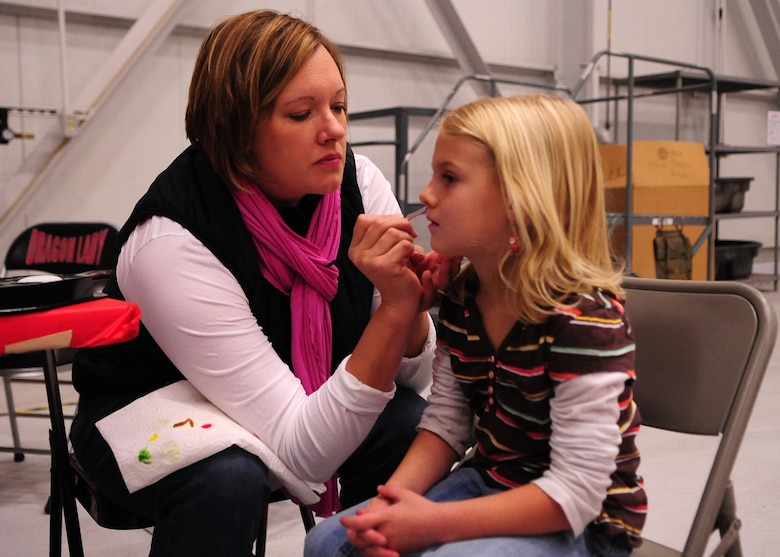 Jenny Yates, a member of Beale's Officer Spouses Club, paints the face of a Beale youth at Dock 6, Beale AFB, Calif., during the Children's Holiday Party Dec. 10. More than 75 volunteers from Beale and the surrounding community worked since before Halloween to make the celebration possible. (U.S. Air Force photo by Senior Airman Shawn Nickel/Released)
