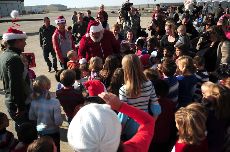 Santa Claus greets Beale youth during the Children's Holiday Party Dec. 10, 2011 at Dock 6, Beale AFB, Calif. The head elf was taxied into dock by an Air Force U-2 Dragon Lady aircraft, sporting nose art portraying Rudolf. (U.S. Air Force photo by Senior Airman Shawn Nickel/Released)