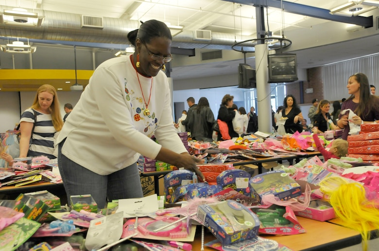 Tech Sgt. Alicia Archie, 162nd Fighter Wing Family Readiness Group volunteer, arranges toys at the Holiday Open House, Dec. 10, in the 162nd Fighter Wing dining facility. (U.S. Air Force photo/Master Sgt. Dave Neve)