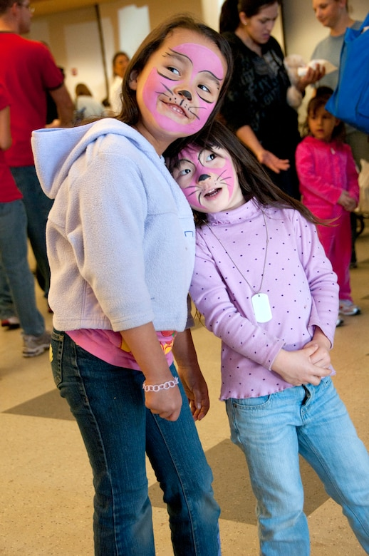 Keahilana Awana, 6, (left) daughter of Tech. Sgt. Leora Awana and Alexis Morgan, 3, daughter of Master Sgt. Dave Morgan get matching face paint at the Holiday Open House, Dec. 10, in the 162nd Fighter Wing dining facility. (U.S. Air Force photo/Master Sgt. Dave Neve)