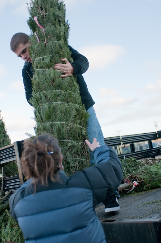Airman First Class Michael Servis of the 102nd Intelligence Wing receives a Christmas tree donated by the Mt. Horeb Masonic Lodge from Dennis, Massachusetts. A total 11 trees were donated to the 102nd on December 4, 2011. (National Guard photo by Senior Airman Jeremy Bowcock/Released)